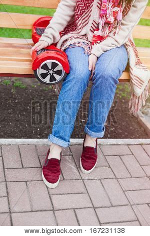 Girl in boho style outfit sitting on a bench with a modern red electric mini segway or hover board scooter. Trending new transportation technology that is so much fun and easy to ride and produces no air pollution to the atmosphere. Focus on the device