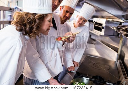 Head chef showing food to his colleagues in the kitchen