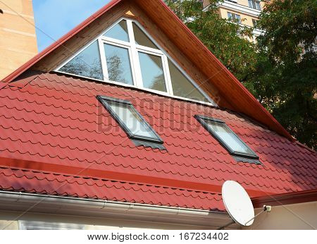 Modern Roof Windows with Skylights and Sun Tunnels. Modern House Construction with metal roof rain gutter system and and roof protection from snow board skylights.