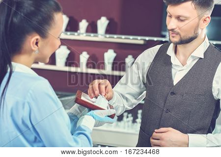 Young brunet man with beard choosing present for his girlfriend at luxury jewelry store. Male holding golden ring with blue stone in hand. Jeweler in gloves showing engagement ring for buyer.