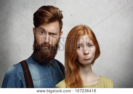 Cute young redhead woman with upset look pouting her lips feeling unhappy with her boyfriend who is standing next to her and frowning looking confused and guilty not knowing what he did wrong