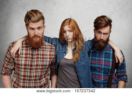Attractive Young Female With Loose Ginger Hairstyle Embracing Two Bearded Hipsters In Stylish Checke