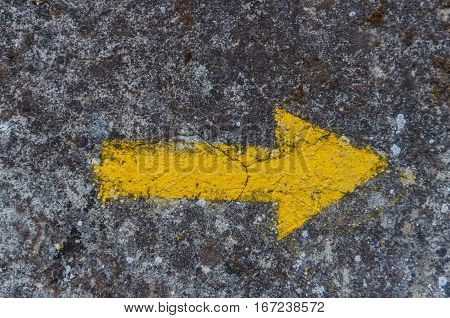 Yellow arrow painted in a wall. Directional sign for pilgrims in Saint james way. Camino de Santiago Galicia Spain