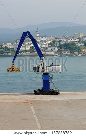 Little harbor crane in blue and yellow. Heavy machinery used in logistics and transport to load and unload goods from ships