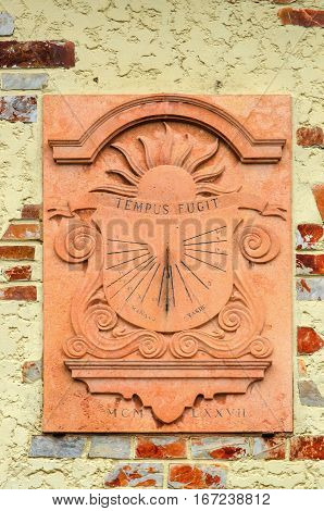 Traditional sundial or sun clock in a wall. Tempus fugit