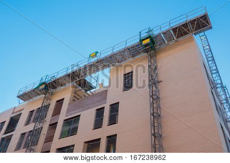 Mechanical scaffolding used in buildings construction. Modern equipment to elevate workers and materials mechanically