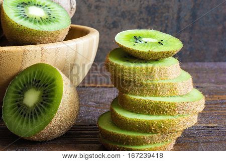 kiwi fruit in a bowl with sliced kiwi pieces on rustic wooden background