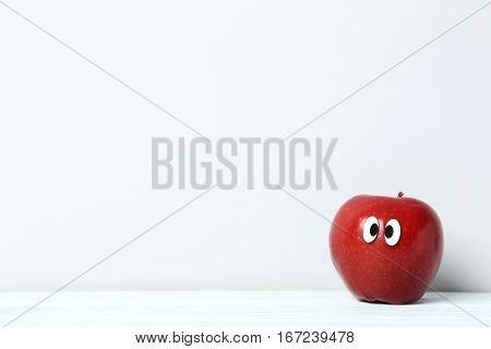 Red Apple With Googly Eyes On Grey Background