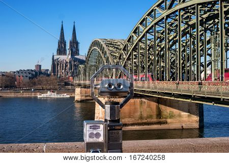Cologne Cathedral and Hohenzollern Bridge. In the foreground of public Binocular Telescope. The Cathedral, built in Gothic style in honor of St. Peter the Apostle and the Virgin Mary.