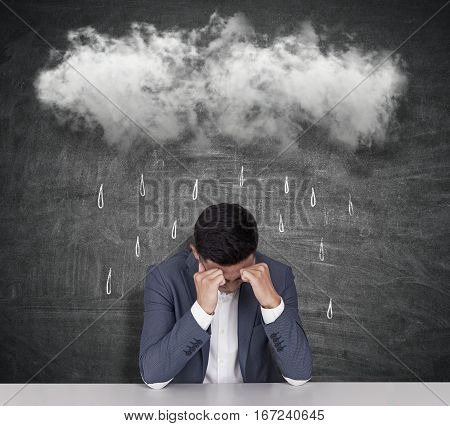 Sad businessman with raining cloud above on chalkboard background. Business failure concept