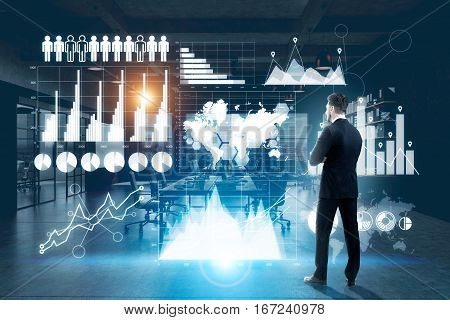 Thoughtful businessman in dark office analyzing digital business panel with charts and diagrams. Economy concept