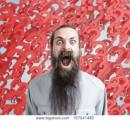 Screaming bearded man stressed because of numerous questions. Abstract red questionmark background. Obsessive compulsive anxiety disorders