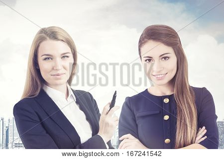 Portrait of two business women in a city. One is blond and holding a marker. The second is smiling and standing with crossed arms.