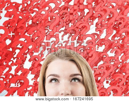 Close up of a woman's head against red question marks background. Concept of multiple questions that need to be answered.