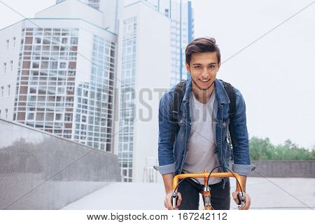 Man riding a bicycle outside. Young guy with backpack looking at camera. He is going to reach the aim. Close up. Urban background