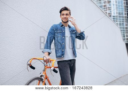 Cheerful young man with beard in blue jeans jacket talking on the mobile phone and smiling while standing near his orange bicycle. Attractive guy is glad to have some conversation with friends. Wall background.