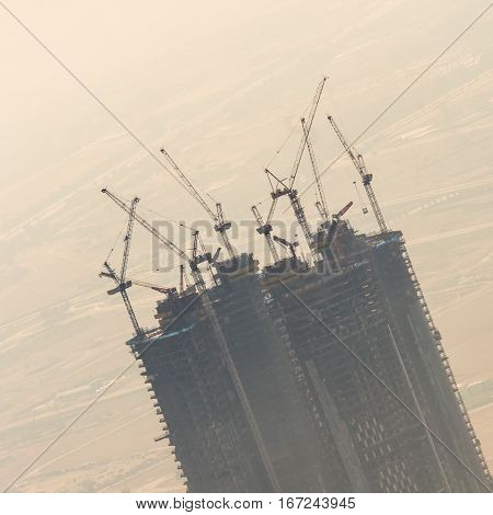 Huge skyscraper construction site with cranes on top of buildings. Rapid urban and construction sector development or inflation of real estate bubble.