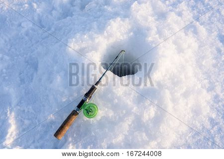 Winter fishing rod lies approximately drilled holes. Winter fishing on the lake.