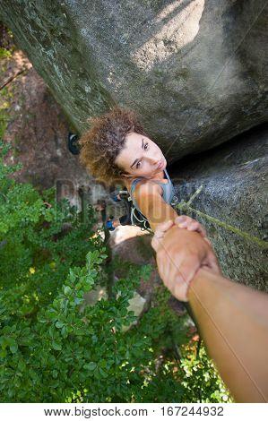 Climber Helping Female Climber To Reach A Peak Of Mountain