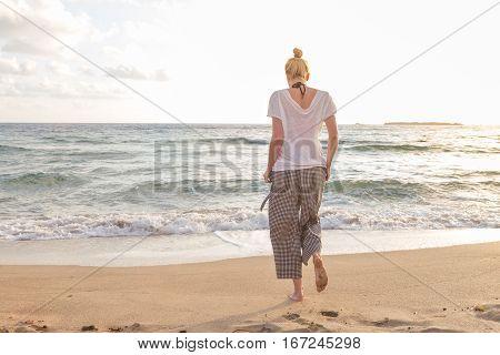 Woman walking on sand beach at golden hour. Seashore sunset walk.