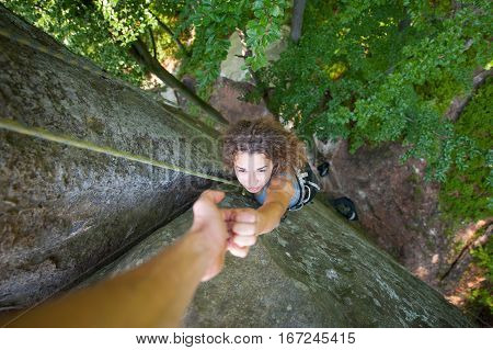 Climber Helping Female Climber To Reach A Top Of Mountain