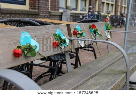 Utrecht the Netherlands - February 13 2016: Red roses on the wooden bench in historic city centre