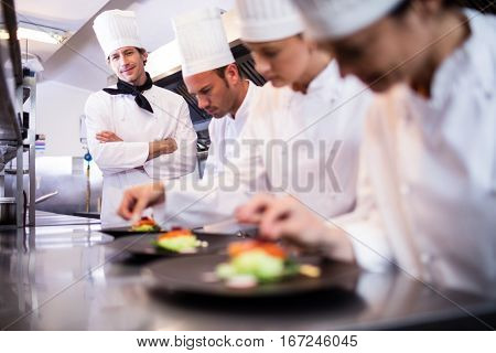 Head chef overlooking other chef preparing dish in the kitchen