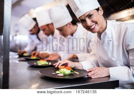 Smiling chef with garnished food plate while other chef decorating dish in the background