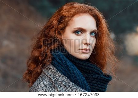 Closeup portrait of beautiful woman with red hair and blue eyes posing outdoors. Red-haired girl. Redhead woman with long curly hair against nature background looking at camera fashion vogue outdoors