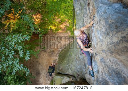 Woman Rock Climber Is Climbing On A Rocky Wall