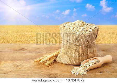 Oat flakes in sack. Ears of oats and oatmeal in bag on table with field on the background. Agriculture and harvest concept. Ripe wheat field, blue sky, sun. Uncooked porridge