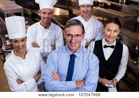Portrait of happy restaurant team standing together with arms crossed in commercial kitchen