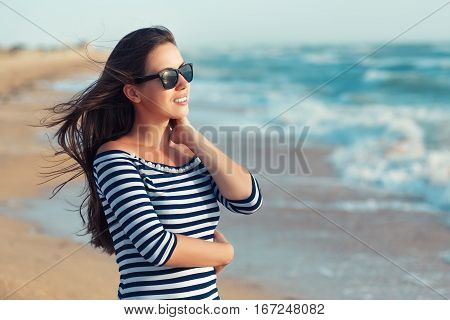 summer holidays and vacation concept. Happy girl standing on the ocean or sea beach. Portrait of stylish woman with tan skin and hair in the wind in striped dress and sunglasses walk on the beach