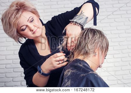 Women's haircut. Hairdresser, beauty salon. Portrait of professional hairdresser middle aged woman making stylish haircut. Process of hair cutting with use thinning scissors. Dynamic shot