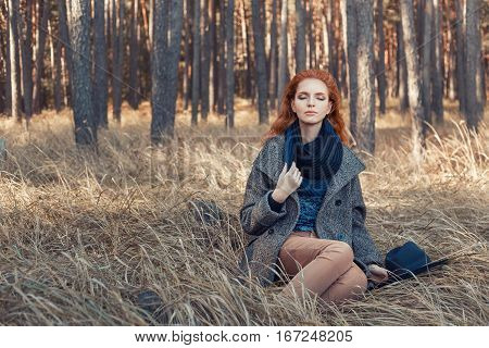 Beautiful red-haired woman. Redhead girl in autumn clothes in the forest. Redhead woman weared knitted scarf, coat. Portrait of dreaming woman with curly red hair outdoors
