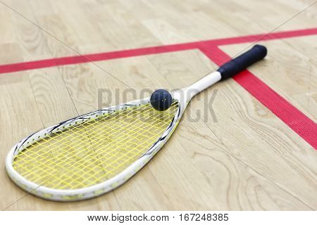 squash racket and ball on the wooden floor. Racquetball equipment on the court next to a red line. Photo with selective focus. Squash time