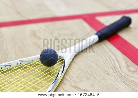 squash racket and ball on the wooden floor. Racquetball equipment on the court next to a red line. Photo with selective focus. Closeup of squash ball on yellow stringed racket