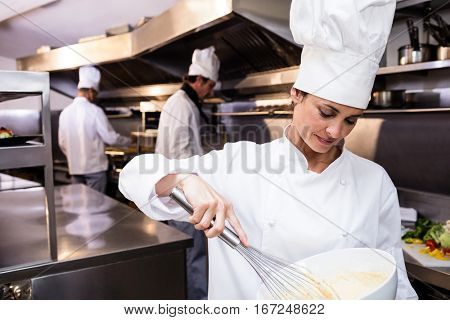 Chef whisking bowl of eggs in a commercial kitchen