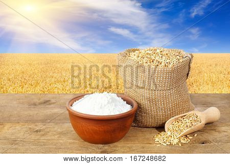 Wheat grains in sack and flour in bowl on table with field of wheat on the background. Agriculture and harvest concept. Ripe wheat field, blue sky, sun