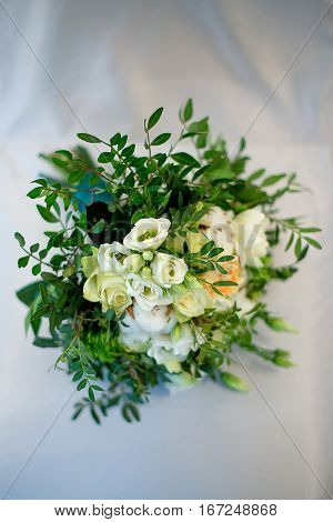The bride's bouquet with branches of pistachio branches of cotton and white roses on a white background. Wedding concept