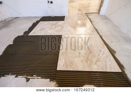 Ceramic tiles. Floor tiles installation. Home improvement renovation - ceramic tile floor adhesive mortar