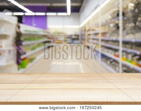 Wooden board empty table in front of of supermarket shelves. Perspective light wood over blur in supermarket. Mock up for display or montage products.