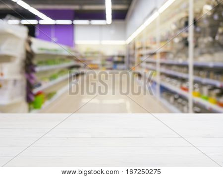 Wooden board empty table in front of of supermarket shelves. Perspective white wood over blur in supermarket. Mock up for display or montage products.