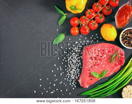Raw meat. Raw beef steak on dark board with fresh herbs, vegetables, seasonings and spices. Top view or flat lay. Copy space