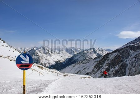 Sign descent on the slopes in the Alpine mountains, the man is going to descend on skis, lots of mountain peaks