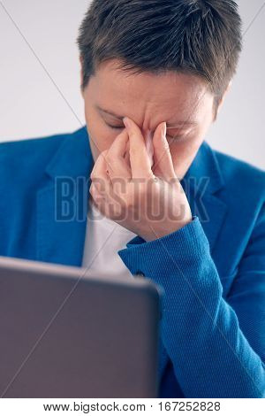 Exhausted businesswoman working overtime on office laptop computer hand on the forehead
