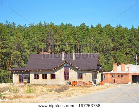Building New Suburban House on the Forest Background. Plastering Wall Metal Roofing Chimney Garage Insulation and Construction Site