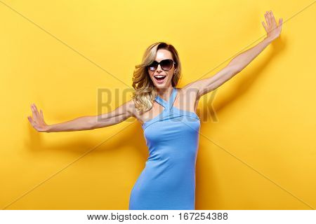 Portrait of excited woman in blue dress and sunglasses with open mouth against of yellow background.Isolated