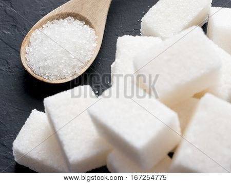background of sugar cubes and sugar in spoon. White sugar on black background. Sugar cubes and granulated in wooden spoon