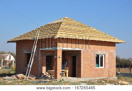 New Roof Membrane Coverings Wooden Construction Home Framing with Roof Rafters and Metal Ladder Outdoor against a Blue Sky. Roofing Construction Exterior with Red Brick house Wall Facade.
